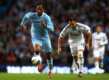 MANCHESTER, ENGLAND - AUGUST 15:  Joleon Lescott of Manchester City beats Stephan Dobbie of Swansea City during the Barclays Premier League match between Manchester City and Swansea City at Etihad Stadium on August 15, 2011 in Manchester, England.  (Photo