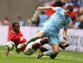 LONDON, ENGLAND - AUGUST 07:  Patrice Evra of Manchester United tackles James Milner of Manchester City during the FA Community Shield match sponsored by McDonald's between Manchester City and Manchester United at Wembley Stadium on August 7, 2011 in Lond
