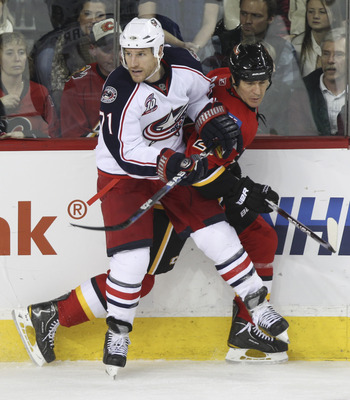 CALGARY, CANADA - MARCH 04:  Steve Staios #27 of the Calgary Flames is pinned to the boards by Chris Clark #71 of  the Columbus Blue Jackets in the third period of NHL action on March 4, 2011 at the Scotiabank Saddledome in Calgary, Alberta, Canada. (Phot