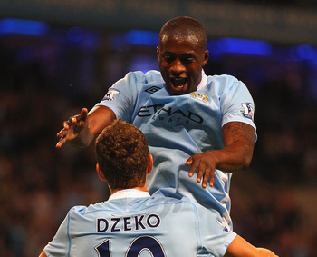 MANCHESTER, ENGLAND - AUGUST 15:  Edin Dzeko of Manchester City celebrates with Yaya Toure after scoring the opening goal during the Barclays Premier League match between Manchester City and Swansea City at Etihad Stadium on August 15, 2011 in Manchester,