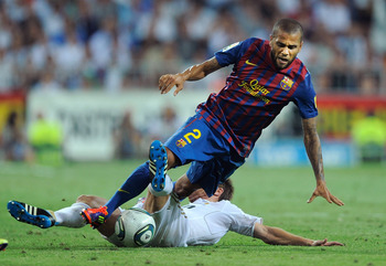 MADRID, SPAIN - AUGUST 14:  Dani Alves (R) of Barcelona is tackled by Xabi Alonso of Real Madrid of Barcelona during the Super Cup first leg match between Real Madrid and Barcelona at Estadio Santiago Bernabeu on August 14, 2011 in Madrid, Spain.  (Photo