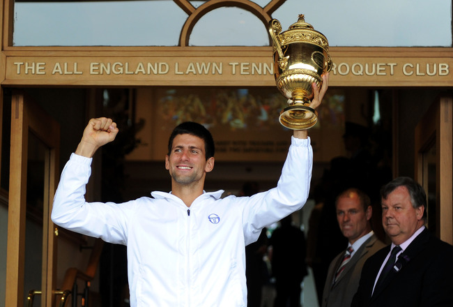 LONDON, ENGLAND - JULY 03:  Novak Djokovic of Serbia holds the championship trophy outside the members entrance after winning his final round Gentlemen's match against Rafael Nadal of Spain on Day Thirteen of the Wimbledon Lawn Tennis Championships at the