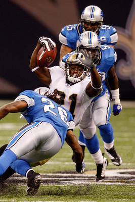 NEW ORLEANS - SEPTEMBER 13:  Mike Bell #21 of the New Orleans Saints is tackled by Louis Delmas #26 of the Detroit Lions at the Louisiana Superdome on September 13, 2009 in New Orleans, Louisiana.  (Photo by Chris Graythen/Getty Images)