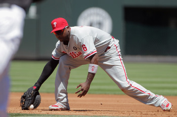 DENVER, CO - AUGUST 03:  First baseman Ryan Howard #6 of the Philadelphia Phillies makes a fielding error on a ground ball by Dexter Fowler #24 of the Colorado Rockies and then made a throwing error on the same play that allowed Eric Young Jr. #1 of the C