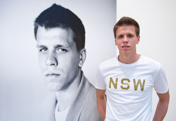 LONDON, ENGLAND - AUGUST 18:   Arsenal Goalkeeper Wojciech Szczesny stands next to his portrait during the official opening Nike's 'The Arsenal: 125' exhibition at the Saatchi Gallery, on August 18, 2011 in London, England. The free exhibition created to