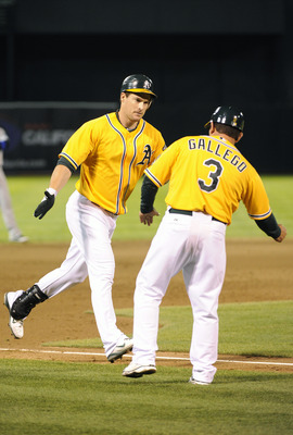 OAKLAND, CA - AUGUST 20: Josh Willingham #16 of the Oakland Athletics celebrates with third base coach Mike Gallego #3 after hitting a two-run home run against the Toronto Blue Jays in the eighth inning during an MLB baseball game August 20, 2011 at the O