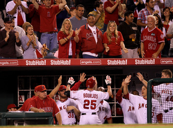 ANAHEIM, CA - AUGUST 20: Peter Bourjos #25 of the Los Angeles Angels of Anaheim is greeted as he returns to the dugout after hitting a solo home run in the seventh inning against the Baltimore Orioles on August 20, 2011 at Angel Stadium in Anaheim, Califo