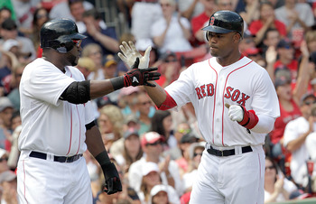 BOSTON, MA  - JULY 24:  Carl Crawford #13 and David Ortiz #34 of the Boston Red Sox celebrate after they both scored against Seattle Mariners at Fenway Park on July 24, 2011 in Boston, Massachusetts.  (Photo by Jim Rogash/Getty Images)
