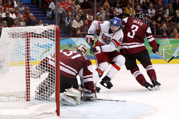 VANCOUVER, BC - FEBRUARY 19:  Jaromir Jagr #68 of Czech Republic attempts a shot on goal against Arvids Rekis #3 and goalkeeper Edgars Masalskis #31 of Latvia during the ice hockey men's preliminary game between Czech Republic and Latvia on day 8 of the V