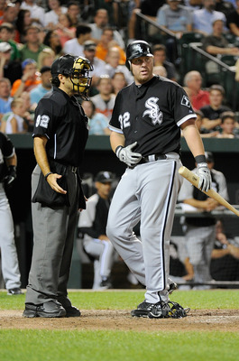 BALTIMORE, MD - AUGUST 10:  Adam Dunn #32 of the Chicago White Sox argues with home plate umpire Bill Miller after striking out in the eighth inning against the Baltimore Orioles at Oriole Park at Camden Yards on August 10, 2011 in Baltimore, Maryland.  (