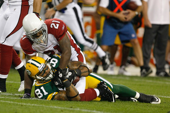 GREEN BAY, WI - AUGUST 19: Andrew Quarless #81 of  the Green Bay Packers is tackled by Patrick Peterson #21 of the Arizona Cardinals in a preseason game at Lambeau Field on August 19, 2011 in Green Bay, Wisconsin. (Photo by Scott Boehm/Getty Images)