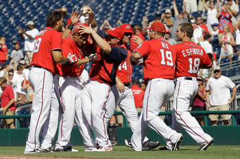 WASHINGTON, DC - JULY 31: Ian Desmond #6 of the Washington Nationals is mobbed by teammates after driving in the winning run against the New York Mets during the ninth inning at Nationals Park on July 31, 2011 in Washington, DC. The Nationals won 3-2.  (P