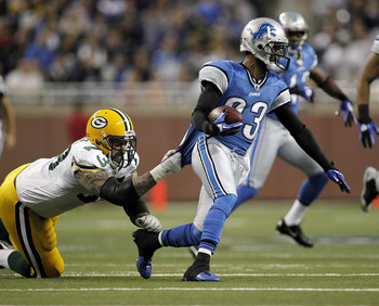 DETROIT, MI - DECEMBER 12:  Chris Houston #23 of the Detroit Lions tries to get around the tackle after picking up a first quarter fumble of Daryn Colledge #73 of the Green Bay Packers on December 12, 2010 at Ford Field in Detroit, Michigan.  (Photo by Gr