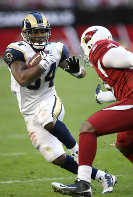 GLENDALE, AZ - DECEMBER 27: Running back Kenneth Darby #34 of the St. Louis Rams carries the ball against linebacker Karlos Dansby #58 of the Arizona Cardinals on December 27, 2009 at University of Phoenix Stadium in Glendale, Arizona.  The Cardinals won