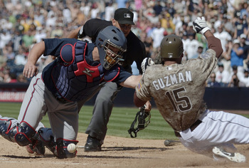 SAN DIEGO, CA - JUNE 26: Jesus Guzman #15 of the San Diego Padres scores past the tag of David Ross #8 of the Atlanta Braves during the eighth inning of a baseball game at Petco Park on June 26, 2011 in San Diego, California.  (Photo by Denis Poroy/Getty