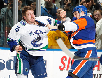 UNIONDALE, NY - JANUARY 11:  Tanner Glass #15 of the Vancouver Canucks fights with Matt Martin #17 of the New York Islanders during an NHL game at the Nassau Coliseum on January 11, 2011 in Uniondale, New York.  (Photo by Paul Bereswill/Getty Images)