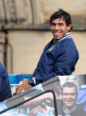 MANCHESTER, ENGLAND - MAY 23:  Carlos Tevez of Manchester City looks on from the back of the bus during the Manchester City FA Cup Winners Parade at Manchester Town Hall on May 23, 2011 in Manchester, United Kingdom.  (Photo by Chris Brunskill/Getty Image