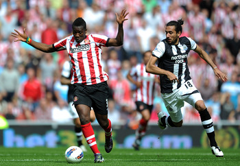 Sunderland striker Asamoah Gyan, left, and Newcastle's Jonas Gutierrez in action on Saturday