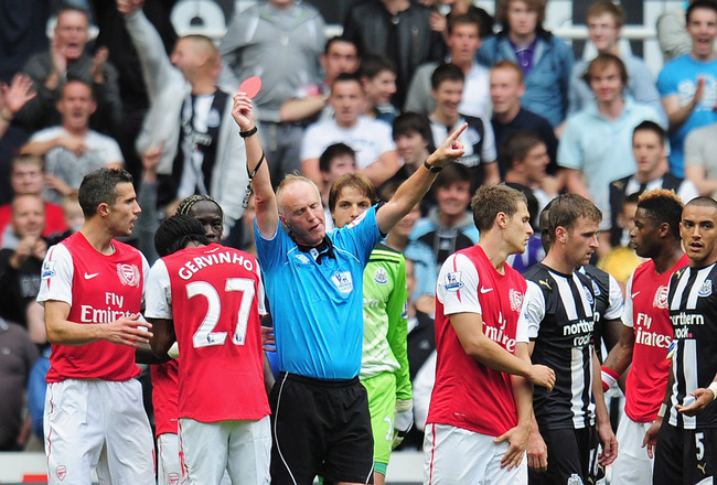 NEWCASTLE UPON TYNE, ENGLAND - AUGUST 13: Gervinho of Arsenal bows his head after being shown the red card by referee Peter Walton during the Barclays Premier League match between Newcastle United and Arsenal at St James' Park on August 13, 2011 in Newcas