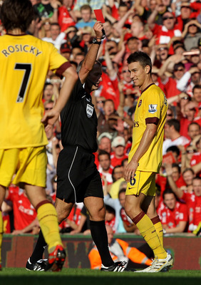 LIVERPOOL, ENGLAND - AUGUST 15:  Referee Martin Atkinson shows a red card to Laurent Koscielny of Arsenal during the Barclays Premier League match between Liverpool and Arsenal at Anfield on August 15, 2010 in Liverpool, England.  (Photo by Clive Brunskil