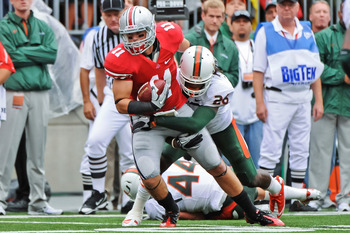 COLUMBUS, OH - SEPTEMBER 11:  Jake Stoneburner #11 of the Ohio State Buckeyes attempts to gain extra yardage after catching a pass against the Miami Hurricanes at Ohio Stadium on September 11, 2010 in Columbus, Ohio.  (Photo by Jamie Sabau/Getty Images)
