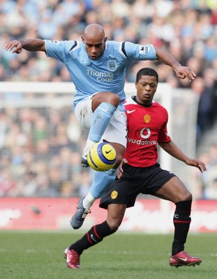 MANCHESTER, UNITED KINGDOM - JANUARY 14:  Trevor Sinclair of Manchester City beats Patrice Evra of Manchester United during the Barclays Premiership match between Manchester City and Manchester United at the City of Manchester Stadium on January 14, 2006