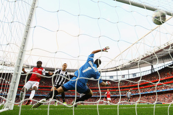 LONDON, ENGLAND - AUGUST 16:  The ball passes Samir Handanovic of Udinese and into the net after a shot by goalscorer Theo Walcott of Arsenal (out of frame) during the UEFA Champions League play-off first leg match between Arsenal and Udinese at the Emira