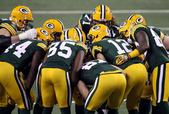 ARLINGTON, TX - FEBRUARY 06: Aaron Rodgers #12 of the Green Bay Packers huddles with teammates during Super Bowl XLV at Cowboys Stadium on February 6, 2011 in Arlington, Texas.  (Photo by Streeter Lecka/Getty Images)