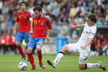 VIBORG, DENMARK - JUNE 22:  Juan Mata (L) of Spain feeds a pass as Pavel Nekhaychik (R) challenges during the UEFA European Under-21 Championship semi-final match between Belarus and Spain at the Viborg Stadium on June 22, 2011 in Viborg, Denmark.  (Photo