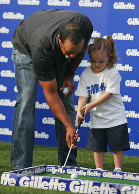 MELBOURNE, AUSTRALIA - NOVEMBER 11:  Golfer Tiger Woods (L) helps a young girl play golf during the launch of the Gillette Champions Junior Education Grant at the Crown Entertainment Complex on November 11, 2009 in Melbourne, Australia.  (Photo by Scott B