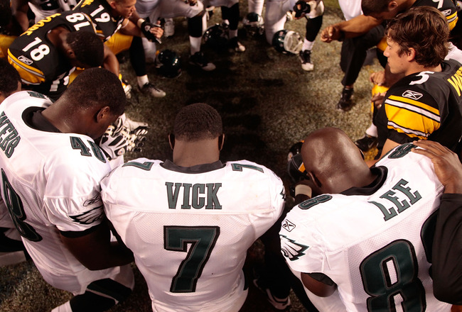 PITTSBURGH - AUGUST 18:  Michael Vick #7, Martell Webb #48, and Donald Lee #88 of the Philadelphia Eagles pray with members of the Pittsburgh Steelers following their preseason game on August 18, 2011 at Heinz Field in Pittsburgh, Pennsylvania.  (Photo by
