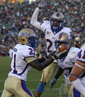 SOUTH BEND, IN - OCTOBER 30: John Flanders #21 of the Tulsa Golden Hurricane holds the ball after intercepting a pass in the end zone against the Notre Dame Fighting Irish as teammates Charles Davis #24 (center) and DeWitt Jennings #27 join the celebratio