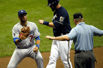 MILWAUKEE, WI - AUGUST 17: James Loney #7 of the Los Angeles Dodgers shows the baseball to umpire Mike Muchinski who signals safe as Casey McGehee #14 of the Milwaukee Brewers steps on the base at Miller Park on August 17, 2011 in Milwaukee, Wisconsin. (P
