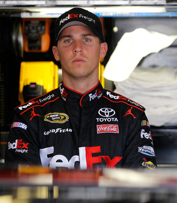 BROOKLYN, MI - AUGUST 20:  Denny Hamlin, driver of the #11 FedEx Freight Toyota, stands in the garage area prior to practice for the NASCAR Sprint Cup Series Pure Michigan 400 at Michigan International Speedway on August 20, 2011 in Brooklyn, Michigan.  (