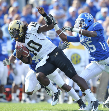LEXINGTON, KY - NOVEMBER 13:  Larry Smith #10 of the Vanderbilt Commodores is pushed down by Martavius Neloms #15 of the Kentucky Wildcats during the game against  at Commonwealth Stadium on November 13, 2010 in Lexington, Kentucky.  (Photo by Andy Lyons/