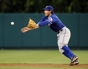 ANAHEIM, CA - AUGUST 15:  Ian Kinsler #5 of the Texas Rangers tosses makes a play to second base against the Los Angeles Angels of Anaheim at Angel Stadium of Anaheim on August 15, 2011 in Anaheim, California.  (Photo by Harry How/Getty Images)