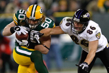 GREEN BAY, WI - DECEMBER 7: Linebacker A.J. Hawk #50 of the Green Bay Packers intercepts the football as tight end Todd Heap #86 of the Baltimore Ravens reaches for the ball at Lambeau Field on December 7, 2009 in Green Bay, Wisconsin. The Packers defeate