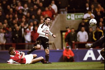 14 Apr 1999:  Ryan Giggs of Manchester United beats the despairing lunge of Tony Adams of Arsenal to drive the ball past David Seaman to score the winner in the FA Cup Semi Final match played at Villa Park in Birmingham. Manchester United won the game 2-1