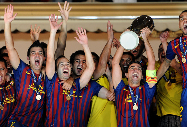 MONACO - AUGUST 26:  Xavi Hernandez (2nd R) of FC Barcelona holds the trophy aloft amid his teammates Alexis Sanchez (L) David Villa (2nd L), Andres Iniesta (3rd L), Cesc Fabregas (4rd L) and Daniel Alves during the UEFA Super Cup match between FC Barcelo