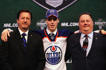 ST PAUL, MN - JUNE 24: (L-R) General Manager Steve Tambellini of the Edmonton Oilers, first overall pick Ryan Nugent-Hopkins of the Edmonton Oilers and a member of the Edmonton Oilers organization stand on the podium for a photo during day one of the 2011