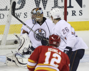 CALGARY, CANADA - APRIL 6: Jarome Iginla #12 of the Calgary Flames score his 40th goal of the season against Nikolai Khabibulin #35 of the Edmonton Oilers as Oilers Kurtis Foster  #26 looks on in second period NHL action on April 6, 2011 at the Scotiabank