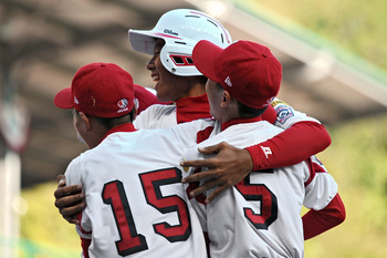 SOUTH WILLAMSPORT, PA - AUGUST 29:  Konan Tomori #28 of the Japan Little League team is hugged by teammates Ryota Norimatsu #15 and Takeshi Saito after hitting a two run homerun in the top of the sixth inning durng the game against the United States on Au