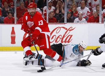 DETROIT - MAY 10: Pavel Datsyuk #13 of the Detroit Red Wings controls the puck in front of Joe Thornton #19 of the San Jose Sharks during the second period in Game Six of the Western Conference Semifinals during the 2011 NHL Stanley Cup Playoffs on May 10