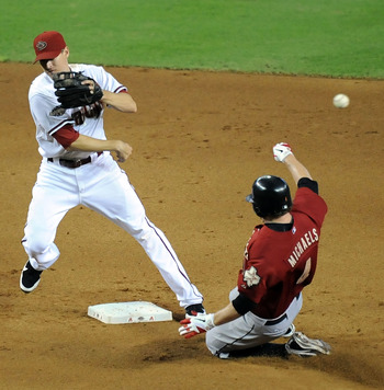 PHOENIX, AZ - AUGUST 11:  Kelly Johnson #2 of the Arizona Diamondbacks attempts to turn a double play over the top of a sliding Jason Michaels #4 of the Houston Astros at Chase Field on August 11, 2011 in Phoenix, Arizona.  (Photo by Norm Hall/Getty Image