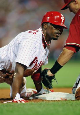 PHILADELPHIA , PA - AUGUST 17:  Jimmy Rollins #11 of the Philadelphia Phillies slides in head first on a double steal against Cody Ransom #1 of the Arizona Diamondbacks at Citizens Bank Park on August 17, 2011 in Philadelphia, Pennsylvania.  (Photo by Len