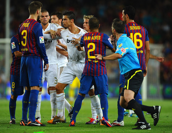 BARCELONA, SPAIN - AUGUST 17:  Cristiano Ronaldo of Real Madrid squares up to Andres Iniesta of Barcelona during the second goal during the Super Cup second leg match between Barcelona and Real Madrid at Nou Camp on August 17, 2011 in Barcelona, Spain.  (