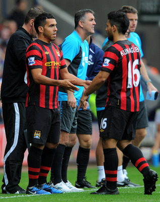 BOLTON, ENGLAND - AUGUST 21:  Carlos Tevez (L) comes on as a substitute for team mate Sergio Aguero of Manchester City during the Barclays Premier League match between Bolton Wanderers and Manchester City at the Reebok Stadium on August 21, 2011 in Bolton