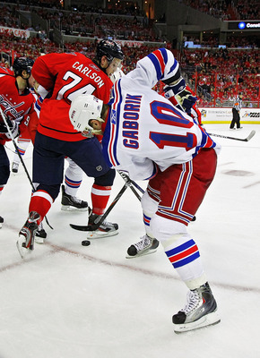 WASHINGTON , DC - APRIL 23:  Marian Gaborik #10 of the New York Rangers battles for the puck behind the back of John Carlson #74 of the Washington Capitals in Game Five of the Eastern Conference Quarterfinals during the 2011 NHL Stanley Cup Playoffs at th