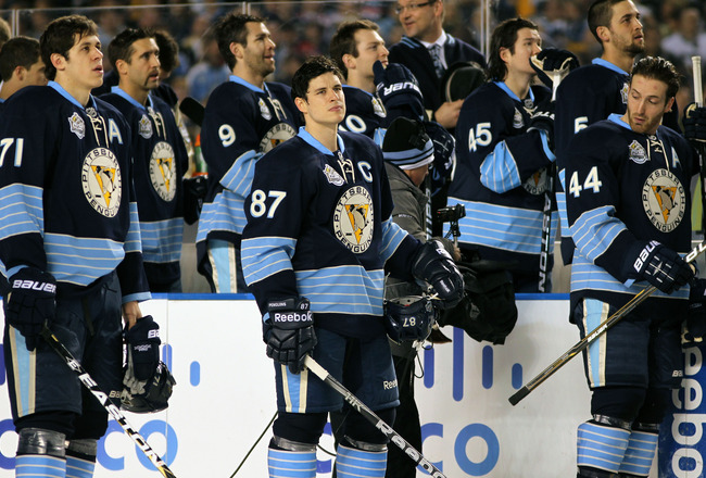 PITTSBURGH, PA - JANUARY 01:  Evgeni Malkin #71, Sidney Crosby #87 and Brooks Orpik #44 of the Pittsburgh Penguins look on during opening ceremonies before the start of the 2011 NHL Bridgestone Winter Classic against the Washington Capitals at Heinz Field