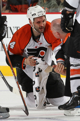 NEWARK, NJ - APRIL 22:  Ian Laperriere #14 of the Philadelphia Flyers reacts after being injured in the second period by Colin White #5 of the New Jersey Devils in Game 5 of the Eastern Conference Quarterfinals during the 2010 NHL Stanley Cup Playoffs at